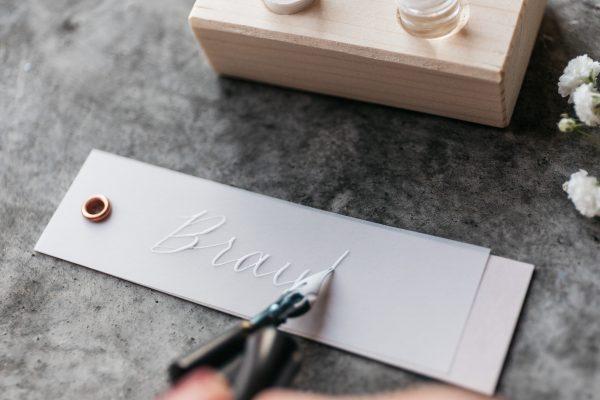 kalligrafierte Platzkarte und Anhänger für Gastgeschenke, weiße Tinte