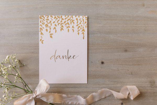 """Postkarte """"danke"""" mit goldener Heißfolienprägung, von oben"""